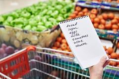 Lista de compras en manos de la mujer en supermercado Fotografía de archivo