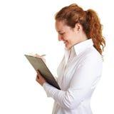 Lista de comprobación que hace tictac de la mujer de negocios encendido Foto de archivo libre de regalías