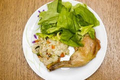 Lista de la pierna de pollo con arroz y ensalada verde Fotografía de archivo