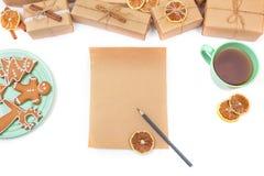 Lista de objetivos pretendidos vazia com presentes do Natal, copo de chá e as cookies caseiros Imagem de Stock