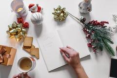 Lista de regalo escrita con una mano en el cuaderno con las decoraciones de los Años Nuevos Imágenes de archivo libres de regalías