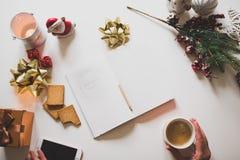 Lista de regalo escrita con una mano en el cuaderno con las decoraciones de los Años Nuevos Imagen de archivo libre de regalías