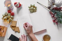 Lista de regalo escrita con una mano en el cuaderno con las decoraciones de los Años Nuevos Imagenes de archivo