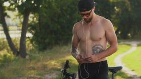 Lista de temas muscular joven de la ojeada del ciclista del hombre en su jugador almacen de video