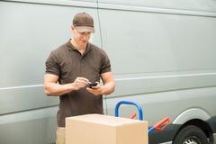 Lista de verificação do homem de entrega no telefone celular Fotografia de Stock Royalty Free