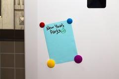 Lista del partido del Año Nuevo de la nota del refrigerador con los imanes fotografía de archivo