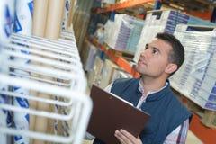 Lista di controllo dell'uomo sulla lavagna per appunti in magazzino Immagine Stock