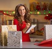 Lista di controllo felice della giovane donna dei regali di Natale Fotografia Stock Libera da Diritti