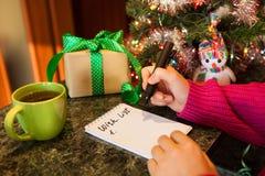 Lista di obiettivi di scrittura della donna, con i presente e l'albero di Natale su fondo Fotografia Stock Libera da Diritti