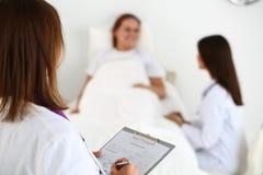 Lista di riempimento d di anamnesi del ricoverato di medico femminile della medicina Immagine Stock Libera da Diritti