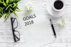 Lista dos objetivos para 2018 Folha de papel perto da pena, dos vidros e da xícara de café no modelo de madeira cinzento da opini imagem de stock