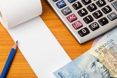 Lista en blanco con los dólares canadienses y la calculadora Imagenes de archivo