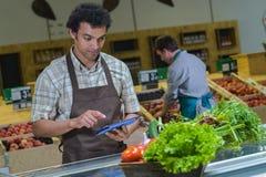 Lista för inventarium för livsmedelsbutikanställd läs- på den digitala minnestavlan royaltyfri fotografi