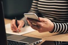 Lista för kvinnahandstilkontakt från telefonen in i affärsdagordning royaltyfri fotografi