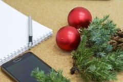 Lista não terminada de objetivos em um caderno em uma tabela de madeira com decorações do Natal e um portátil Imagem de Stock Royalty Free