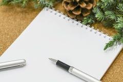 Lista não terminada de objetivos em um caderno em uma tabela de madeira com decorações do Natal e um portátil Imagens de Stock Royalty Free