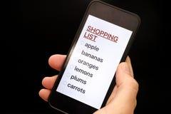 Lista Zakupów na mądrze telefonu pokazie w kobiety ręce zdjęcie royalty free