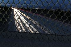 Listando luzes da autoestrada através da cerca do elo de corrente fotografia de stock