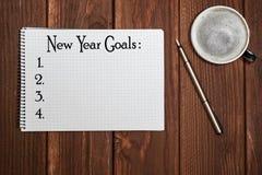 Listar mål för nytt år för bästa sikt med anteckningsboken, kopp kaffe på träskrivbordet fotografering för bildbyråer
