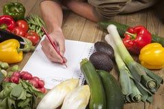 Liste d'écriture de la main de l'homme de légumes organiques Photos libres de droits