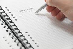 Liste de stratégie d'écriture de main sur le cahier blanc Photographie stock