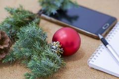 Liste non remplie de buts dans un carnet sur une table en bois avec des décorations de Noël et un ordinateur portable Images stock