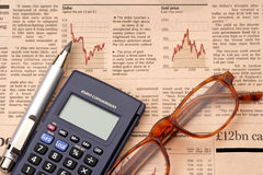 Listed stocks. Financial newspaper with calculator and glasses Stock Photos