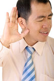 Listen. Businessman listen by gesture with his hand to ear to hear on white background Royalty Free Stock Photography