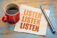 Listen concept on napkin. Listen - communication concept - word abstract on a napkin with a cup of coffee stock photo