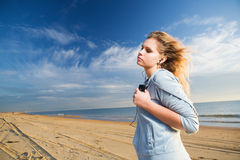 Listen music. Young woman listen music with closed eyes at sunny day at seahore Royalty Free Stock Images