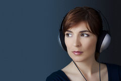 Listen music. Young woman listen music with headphones over a blue wall Stock Photo