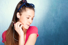 Listen music. Teen girl listen music on earphones, studio shot Royalty Free Stock Photo