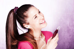 Listen music. Young woman listen music from cell phone with earphones, studio shot Stock Photography