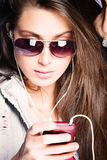 Listen music. Young woman listen music from cell phone with earphones wearing sunglasses, studio shot Stock Photo