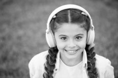 Listen music while relaxing outdoor. Kid girl enjoy music while sit on green grass meadow. Pleasant leisure time. Child. Headphones listen music. Fashion pretty royalty free stock photos