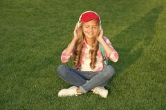 Free Listen Music While Relaxing Outdoors. Kid Girl Enjoy Music Green Grass Meadow. Pleasant Time. Child Headphones Listen Royalty Free Stock Photography - 211022107