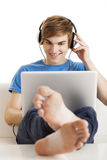 Listen podcast. Young man sitting on the couch and listen podcast over the internet Royalty Free Stock Images