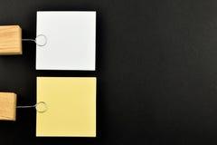 Listen Sie, zwei Papieranmerkungen mit Haltern auf Schwarzem für Darstellung auf Stockfotografie