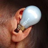 Listen To Ideas. Concept as a light bulb inside a human ear as a symbol of listening and tuning in to creative thoughts and hearing success advice royalty free illustration