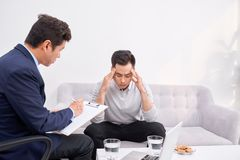 Listen to me. Asian man wrinkling forehead while looking at his therapist stock photo