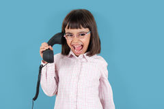 Listen to me. Funny little girl with glasses screaming at retro phone Stock Images