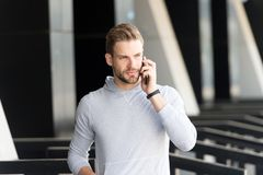 Listen to me. Man beard walks with smartphone, urban background. Man with beard serious face talk smartphone. Guy royalty free stock photo