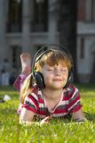Listen to the music. A cute little girl listening the music on a grass in the park Royalty Free Stock Photos