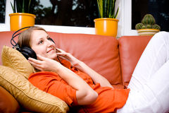 Listen to the music. Young woman listen to the music with head phones Stock Photo