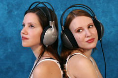 Listen to the music. Two beautiful young woman wearing headphones and listen to music Royalty Free Stock Image