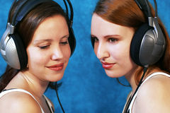 Listen to the music. Two beautiful young woman wearing headphones and listen to music Royalty Free Stock Photos