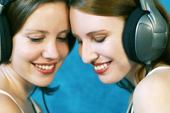 Listen to the music. Two beautiful young woman wearing headphones and listen to music Stock Images