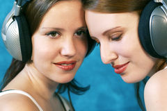 Listen to the music. Two beautiful young woman wearing headphones and listen to music Stock Photography