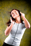 Listen to the music. Young woman listen to the music with head phones Stock Photos
