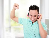 Listen to the music. Smiling young man listening to music in his room Royalty Free Stock Image